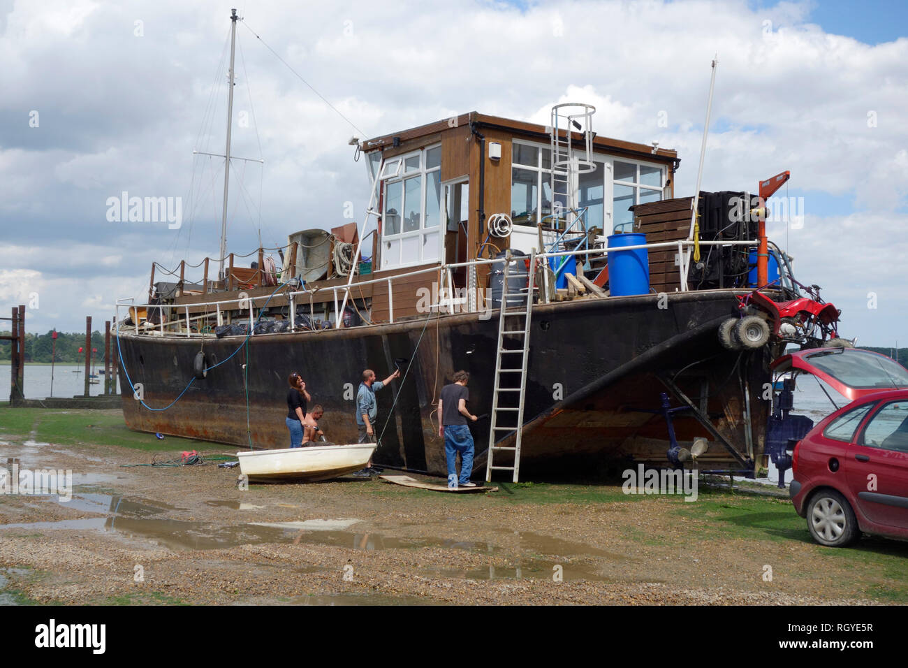 People painting the hull of a barge at Pin Mill, Suffolk - Stock Image