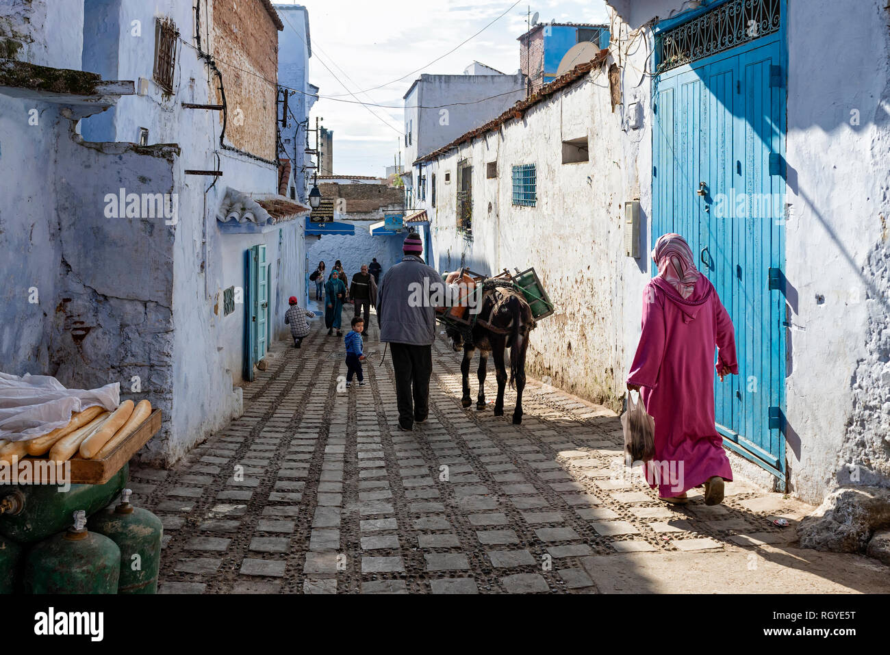 Locals going shopping, working and walking around the old town. Picture of an ordinary day in Chefchaouen, Morocco - Stock Image