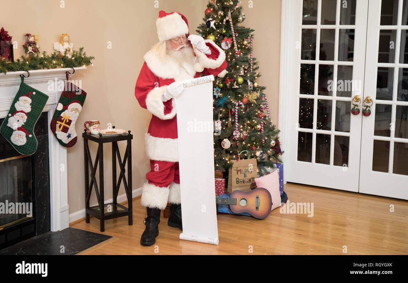 Santa reading his naughty or nice list in a living room decorated for Christmas. Stock Photo