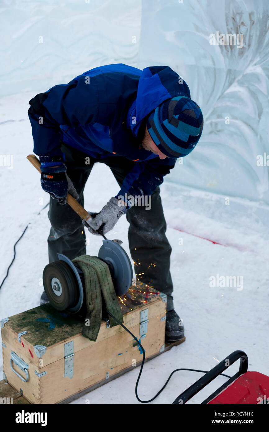 The sculptor sharpens the working tool on the emery wheel - Stock Image