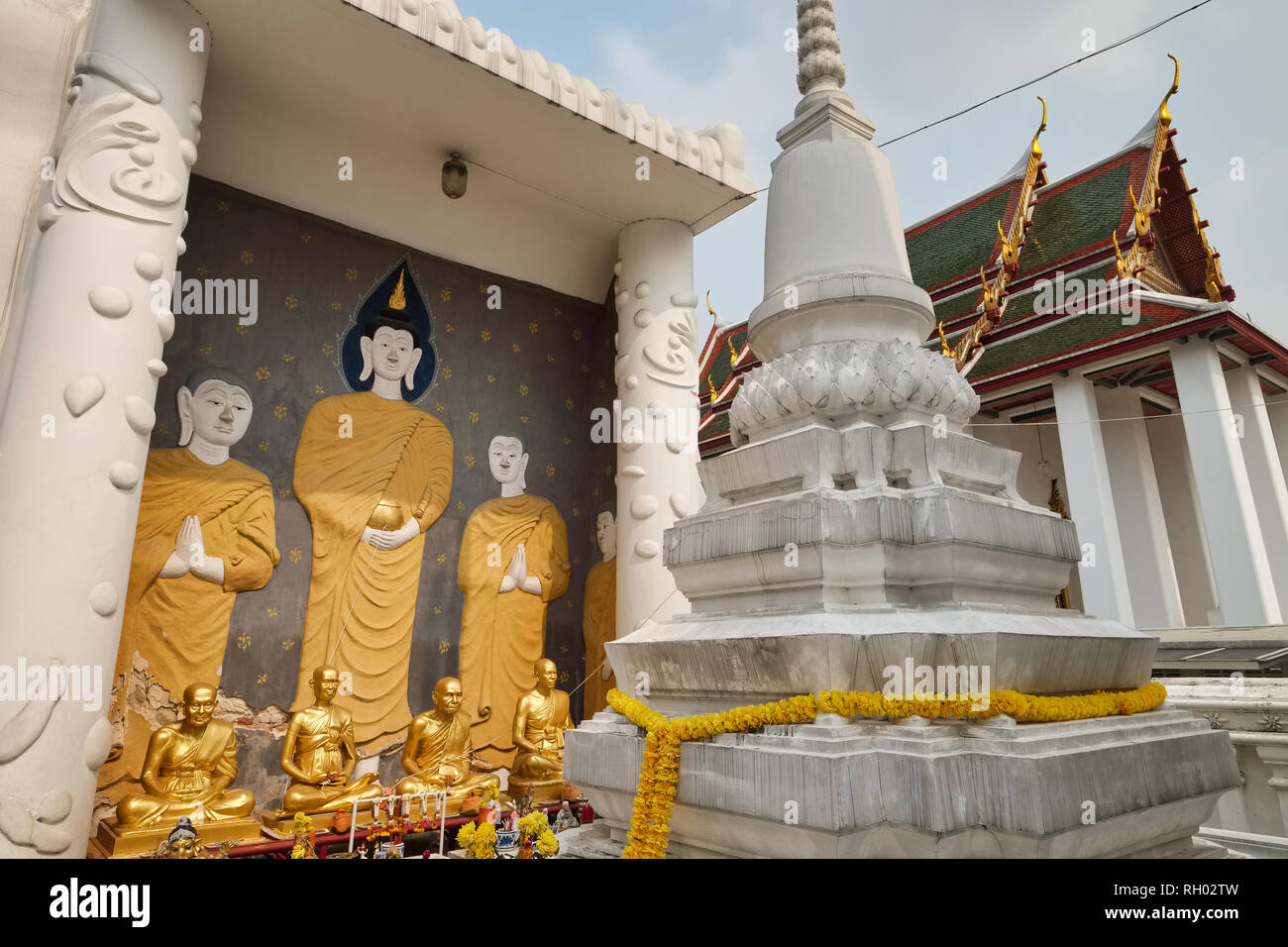 A wall painting of Buddha and his disciples, next to a white chedi or stupa, Wat Ratchanadta, Bangkok, Thailand - Stock Image