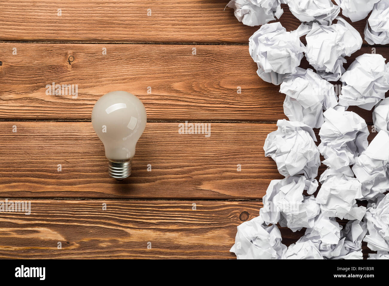 Ideological concept with wastepaper light bulb on wooden table - Stock Image