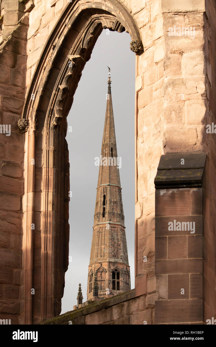The Spire of Holy Trinity Church seen through the windows of Coventry Old Cathedral - Stock Image
