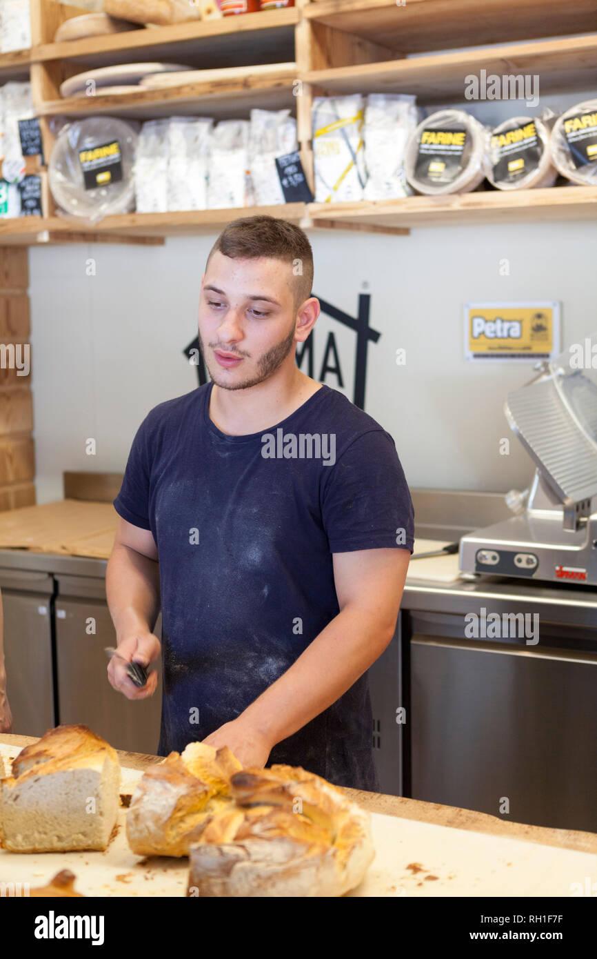 man cutting bread, mercato metropolitano, milan, italy - Stock Image