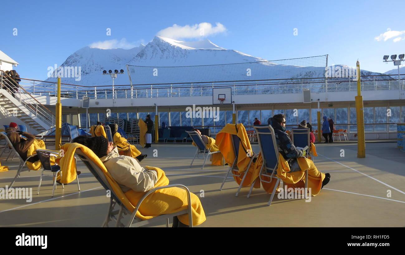 Gäste eines Kreuzfahrtschiffes sitzen in Decken gehüllt und betrachten verschneite Berge. - Stock Image