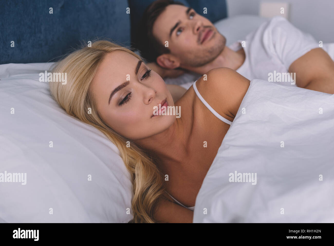 jealous young couple lying together in bed and looking aside, relationship problem concept - Stock Image