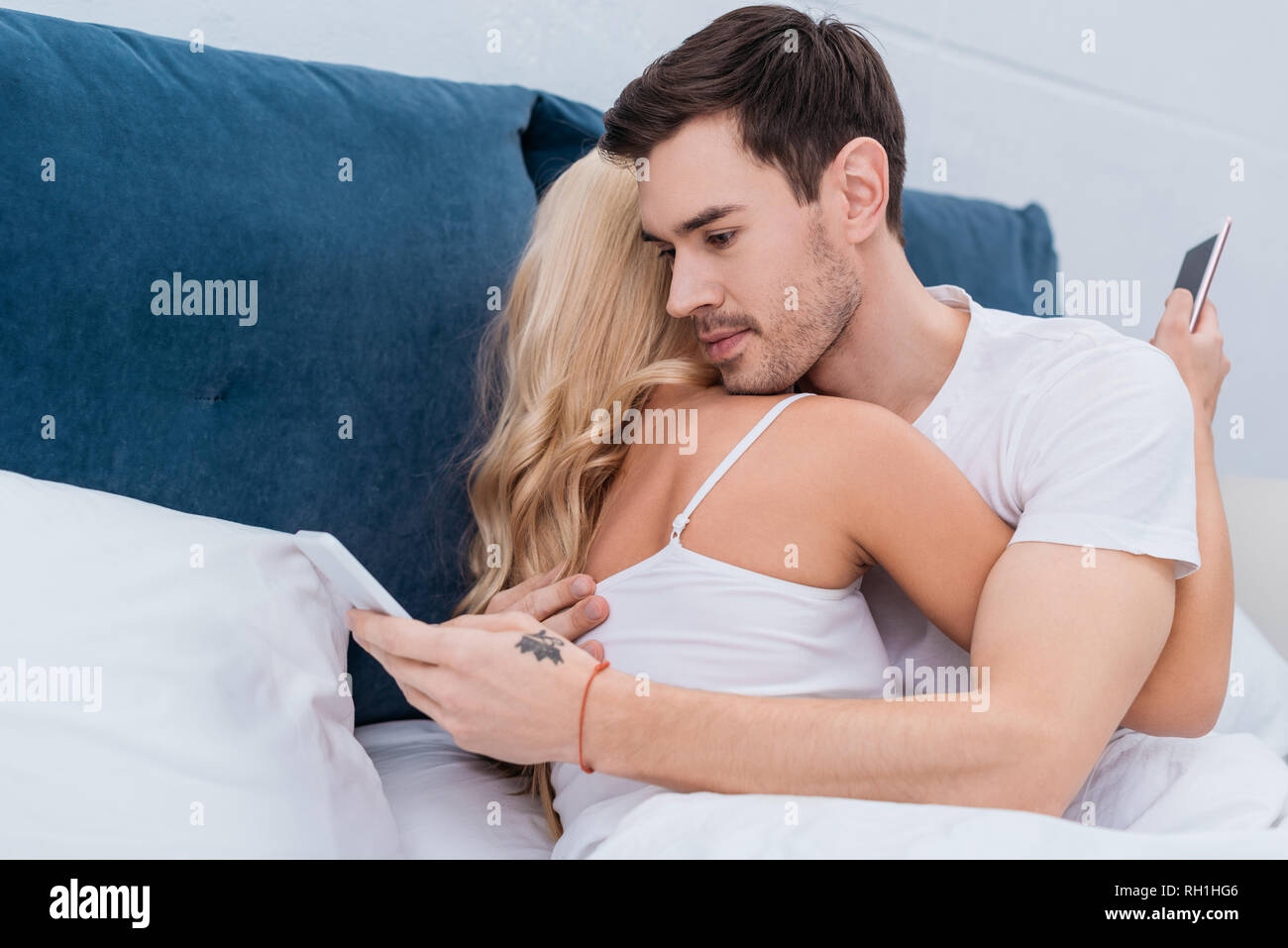 young couple hugging and using smartphones in bed, relationship problem concept - Stock Image