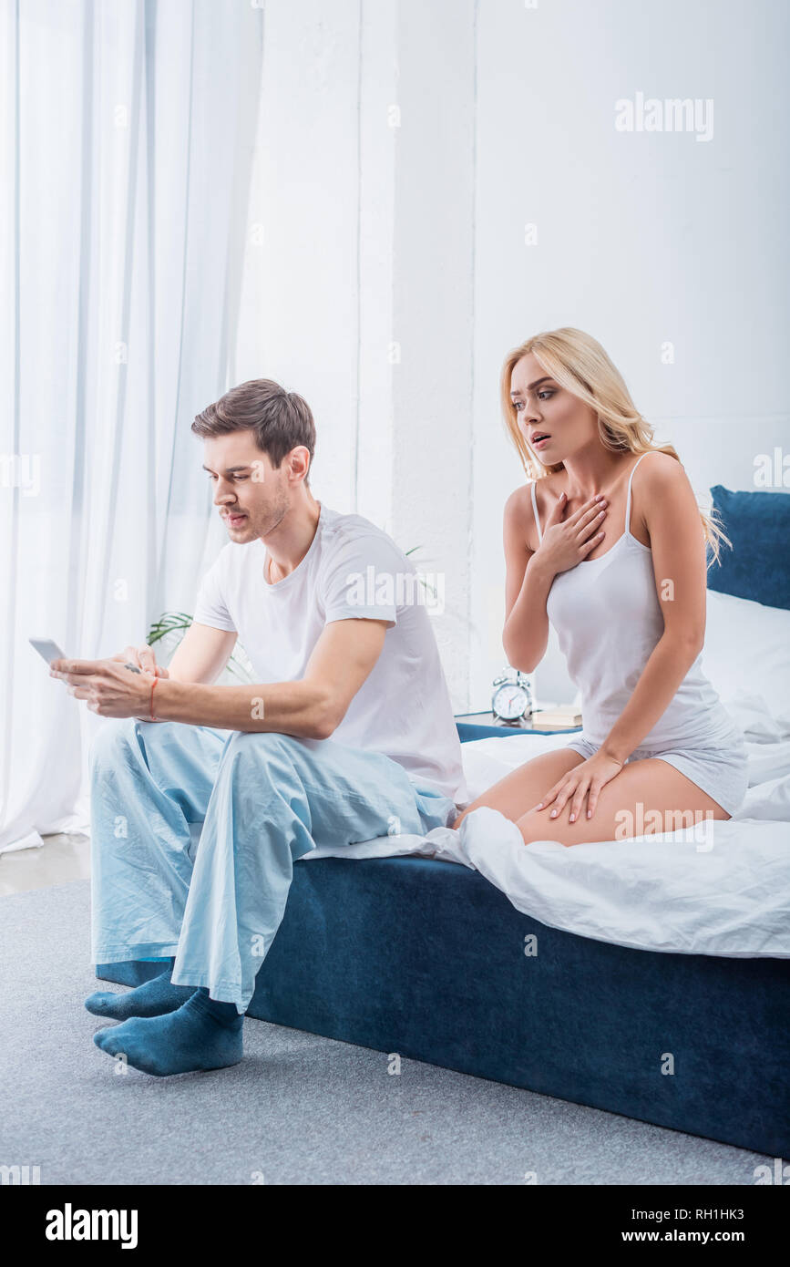 shocked woman looking at husband using smartphone on bed, distrust concept - Stock Image
