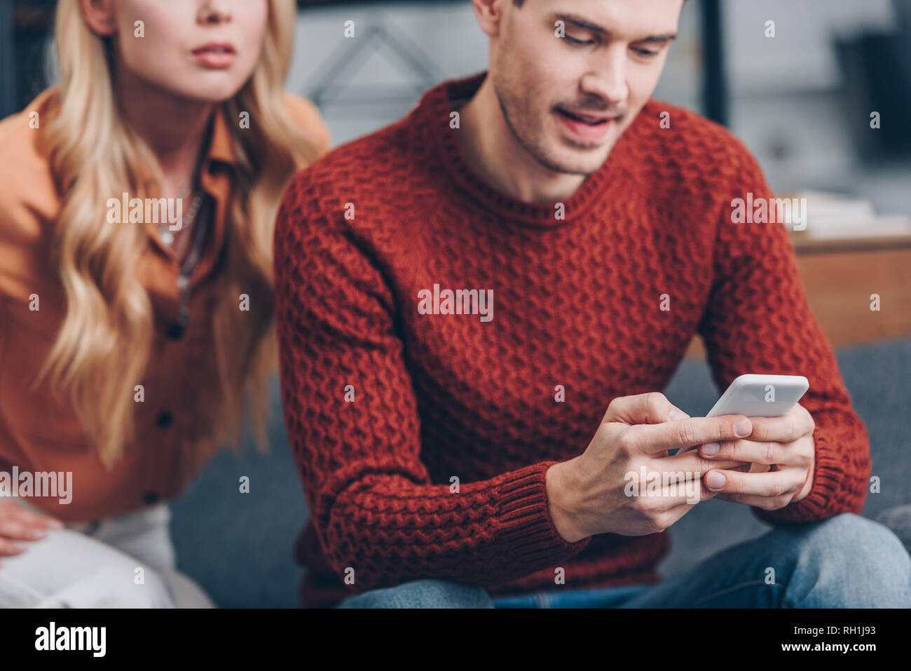 cropped shot of man using smartphone and wife sitting behind, distrust concept - Stock Image