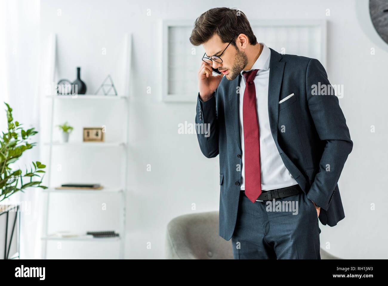 handsome businessman in formal wear talking on smartphone in office - Stock Image