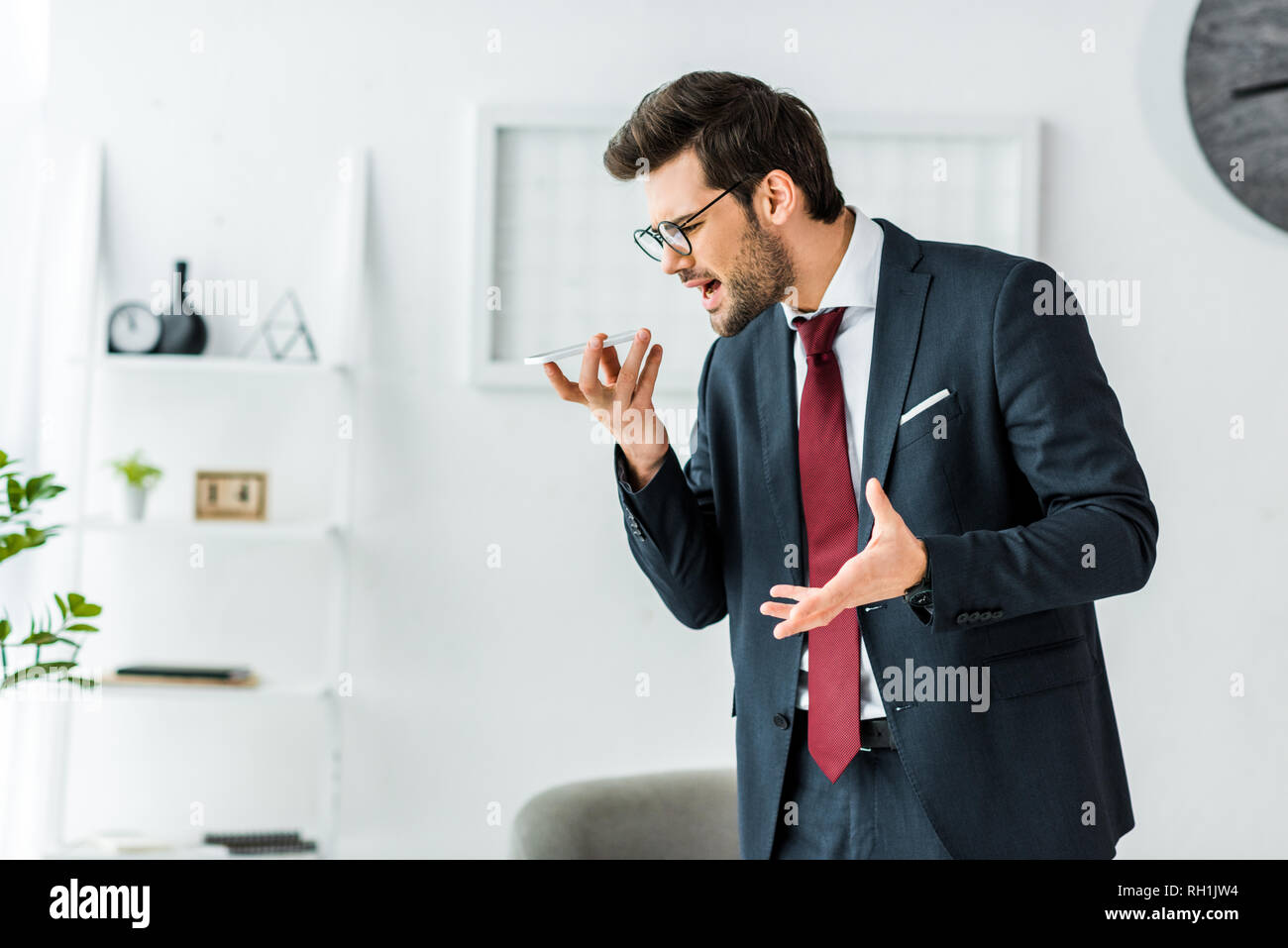 angry businessman in formal wear yelling at smartphone during conversation in office - Stock Image
