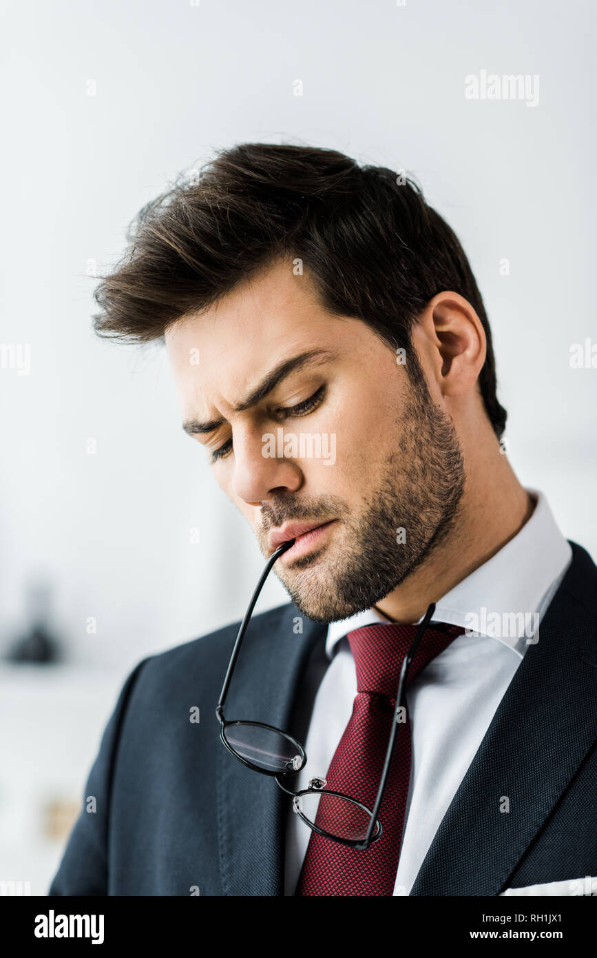 serious handsome businessman in formal wear biting glasses in office - Stock Image