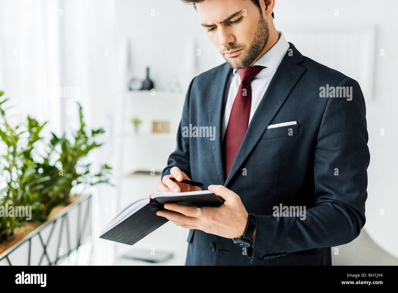 handsome businessman in formal wear writing in notebook in office - Stock Image