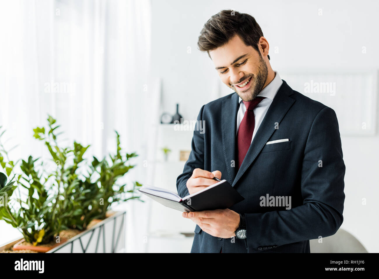 handsome smiling businessman in formal wear writing in notebook in office - Stock Image