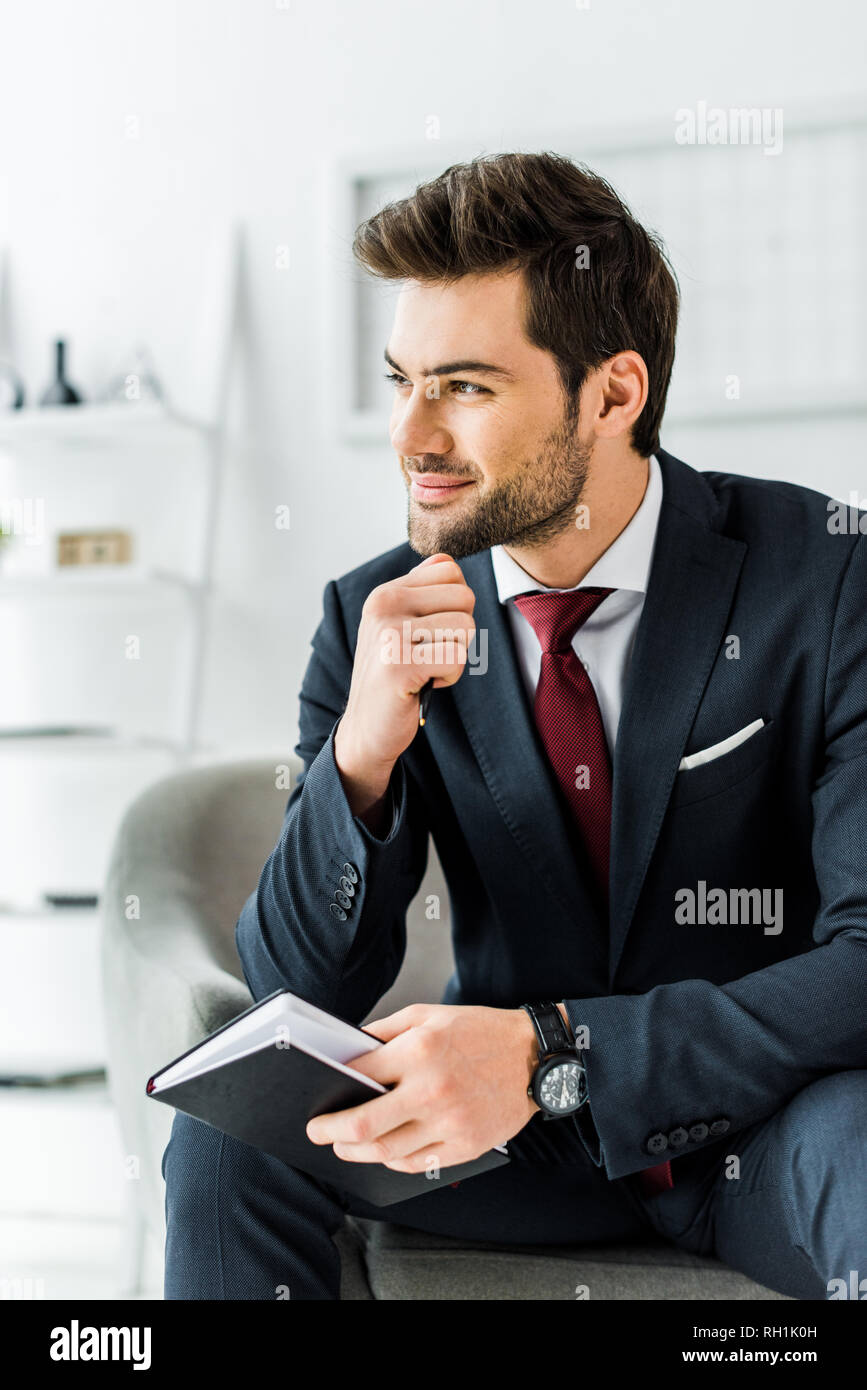 handsome smiling businessman in formal wear sitting with notebook in office - Stock Image