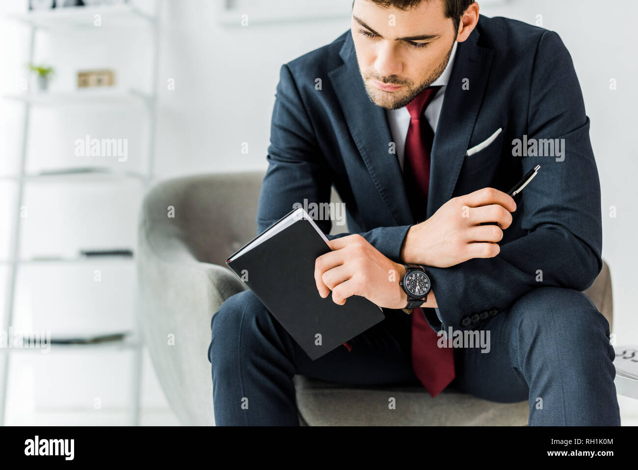 pensive businessman in formal wear sitting and holding notebook in office - Stock Image
