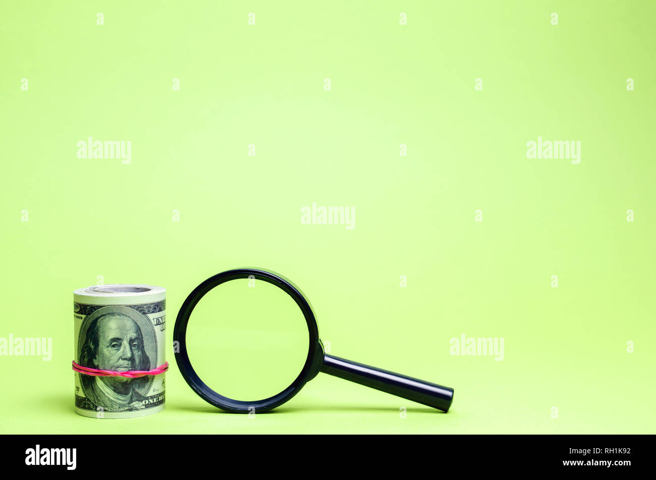 Dollars and magnifying glass. The concept of finding sources of investment and sponsors. Charitable funds. Startups and crowdfunding. Search for avail - Stock Image