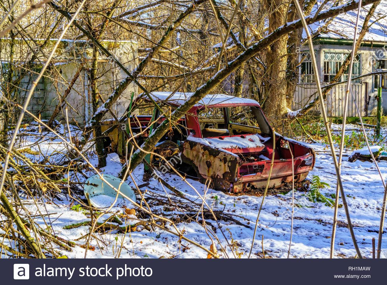 Abandoned red car surrounded by snow in Chernobyl Exclusion zone in Ukraine - Stock Image