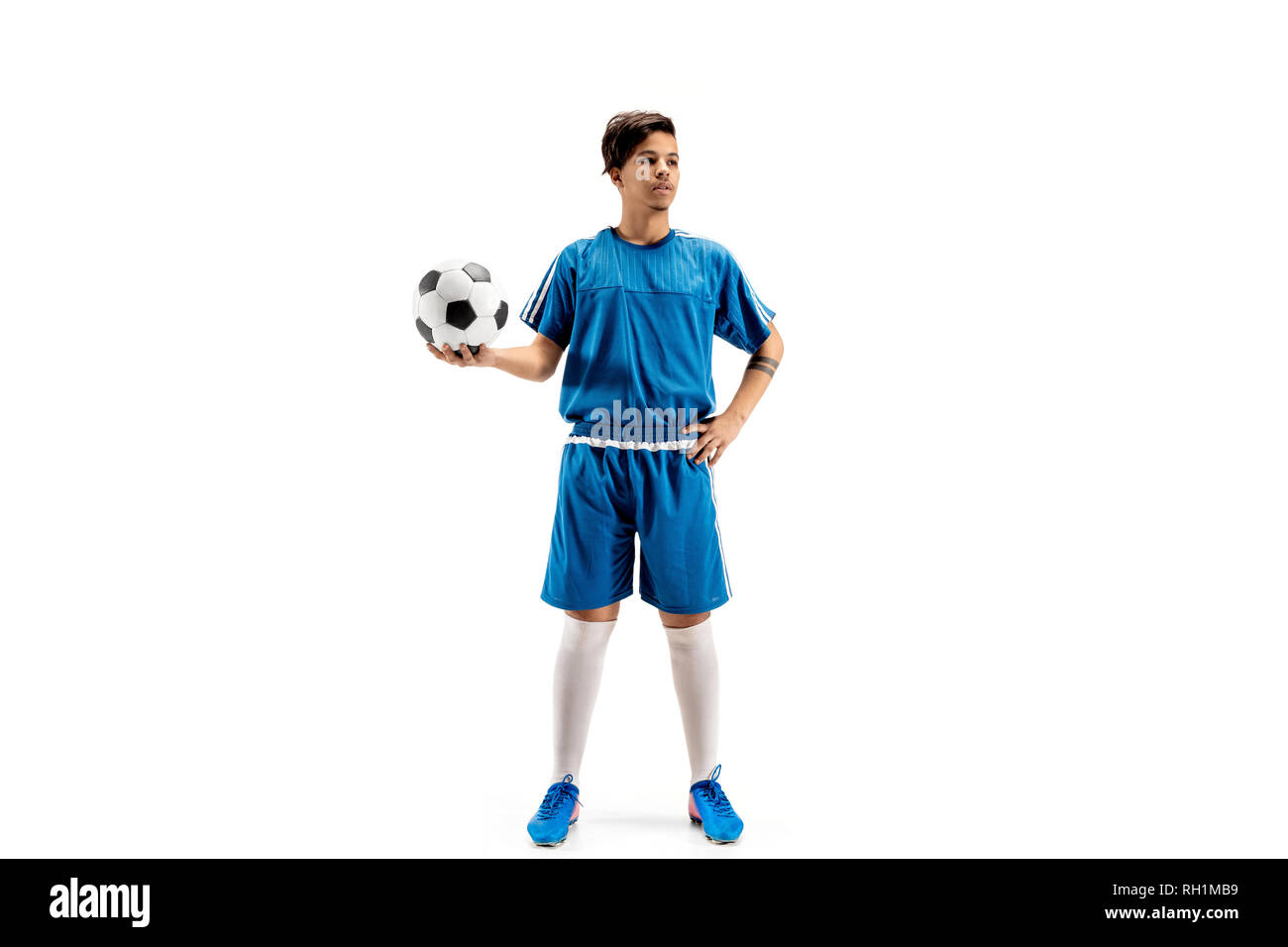 Young fit boy with soccer ball standing isolated on white as winner. The football soccer player on studio background. Stock Photo