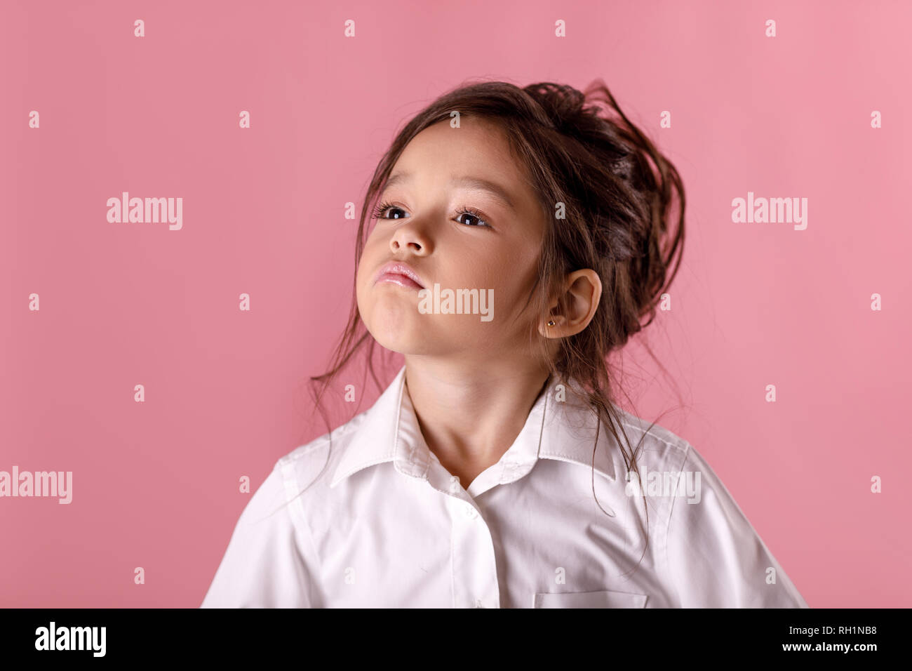 Cute proud little girl in white shirt with hairstyle looking to camera on pink background i am the best human emotions