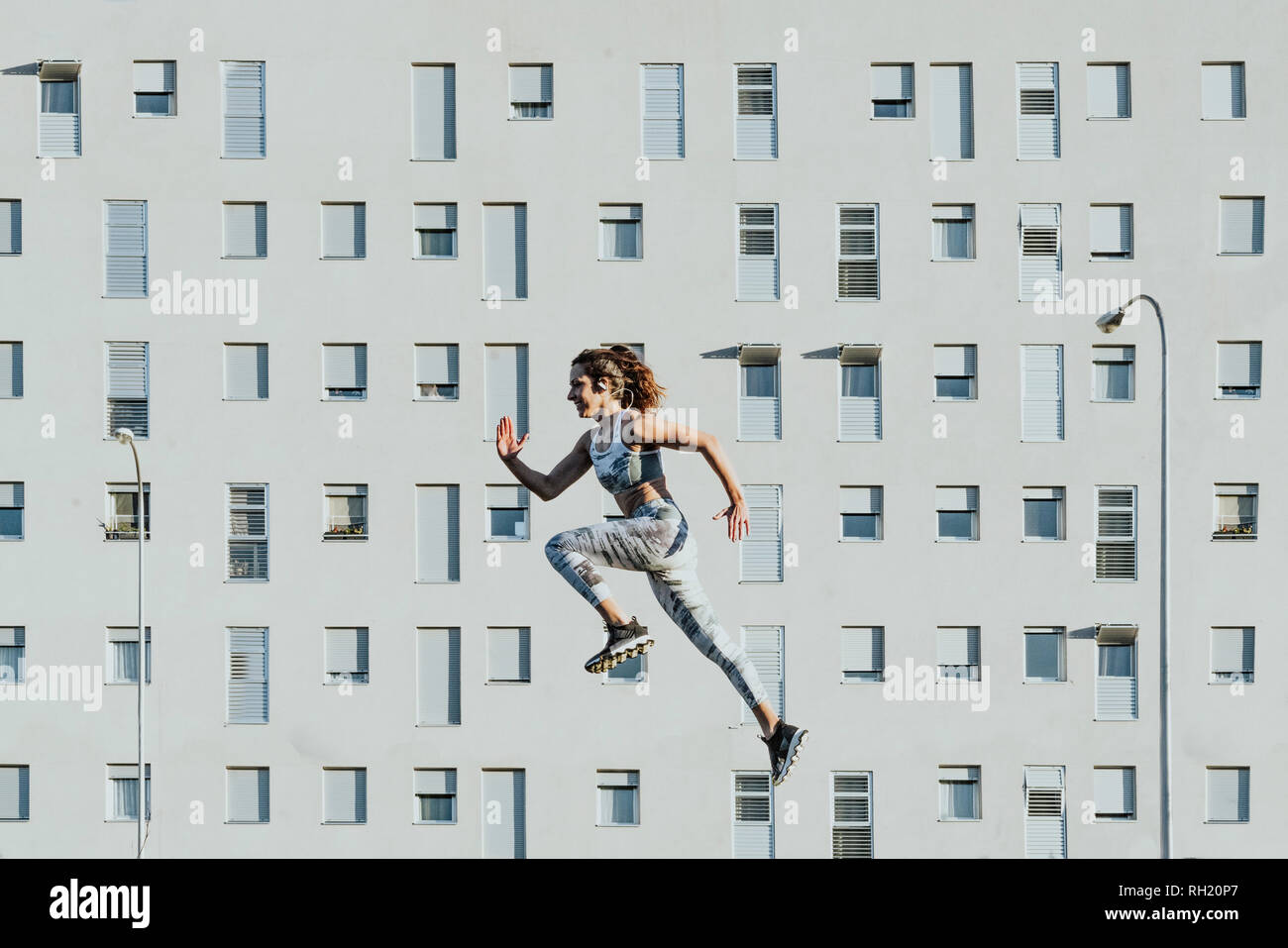 Side view of athletic slim lady levitating near building in sunny weather - Stock Image