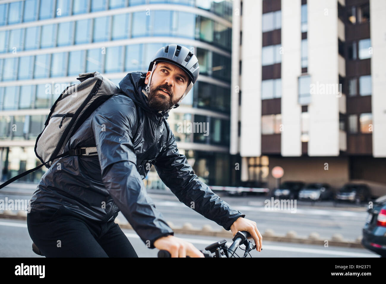 Male hipster courier with bicycle cycling on a road in city, delivering packages. Copy space. Stock Photo