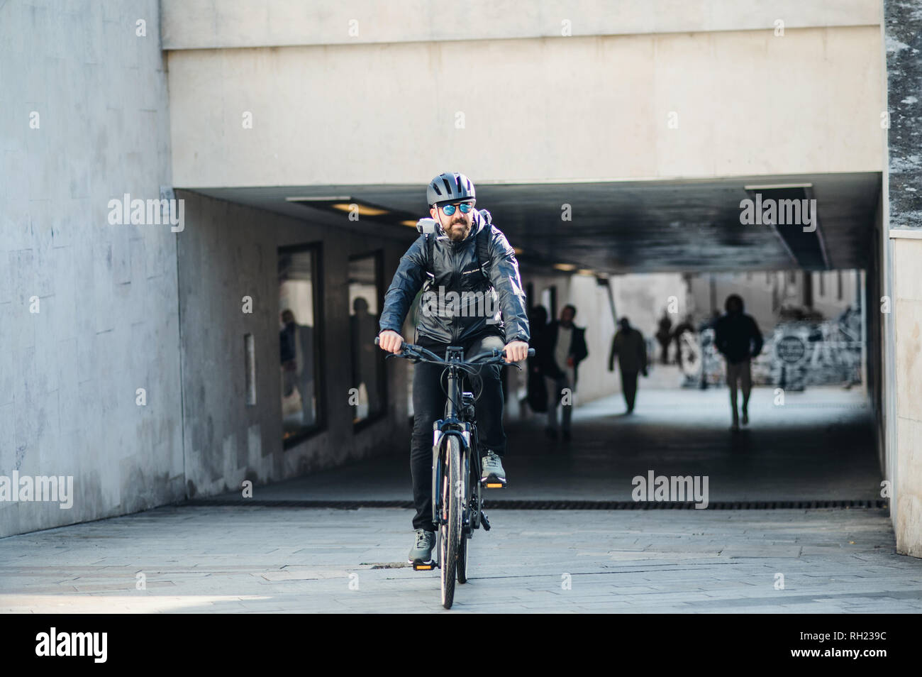 A male bicycle courier cycling in city, delivering packages. Copy space. Stock Photo
