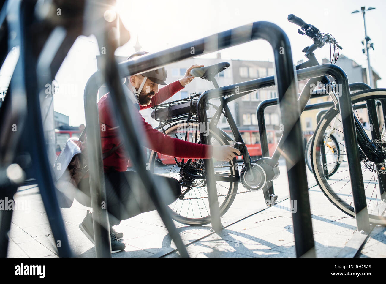 A hipster businessman commuter parking electric bicycle in city when going to work. Stock Photo