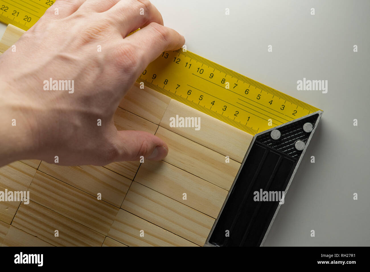Checking the corner of the table, hand with corner ruler and wooden blocks table - Stock Image