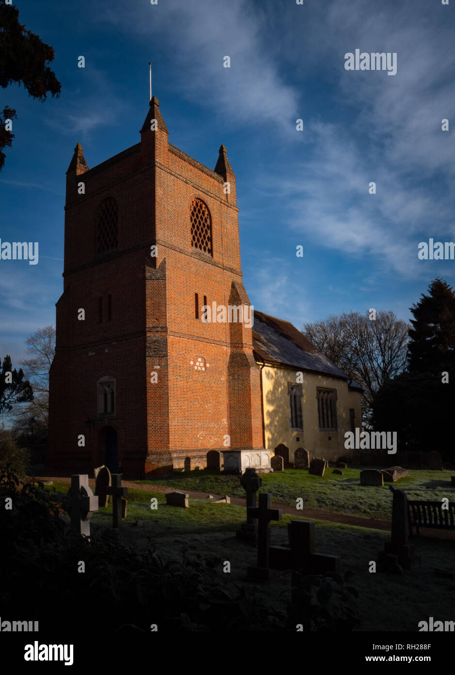 English village church with tower and cemetery with tombstones in early morning sunlight Stock Photo