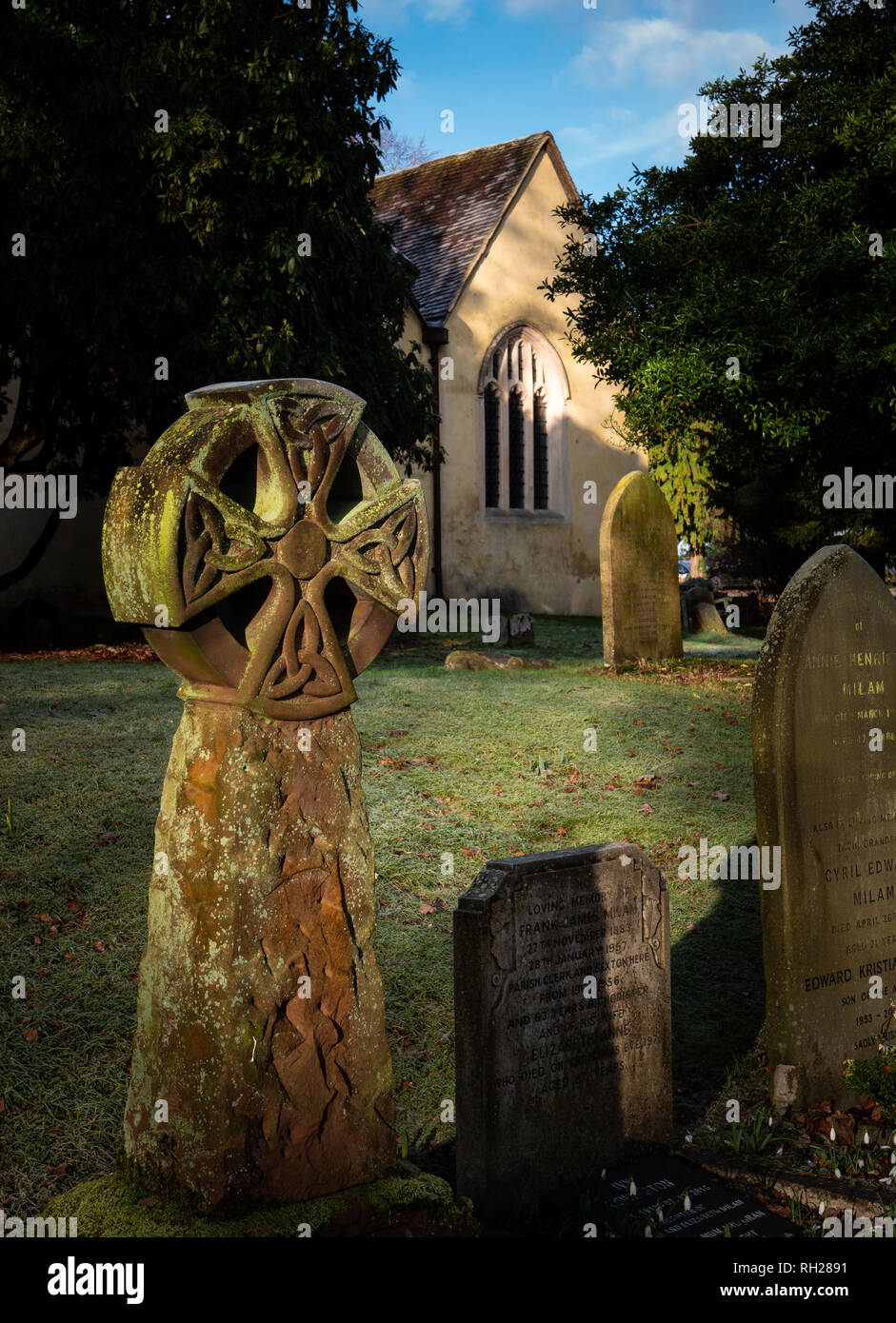 Portrait English village church and cemetery with tombstones in early morning sunlight Stock Photo