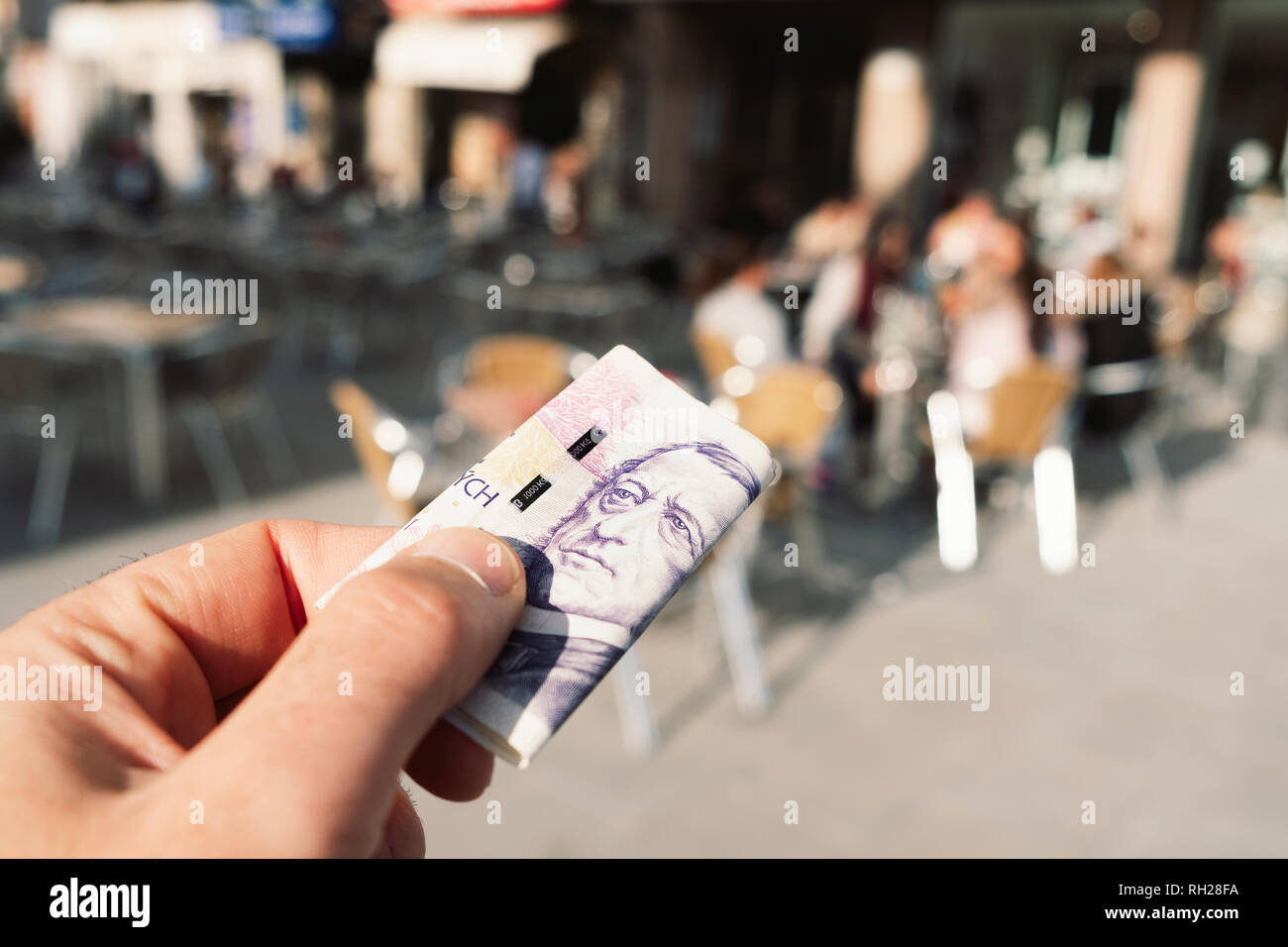 closeup of a young caucasian man on the terrace of a cafe about to pay the bill with czech korunas in Prague, Czech Republic - Stock Image