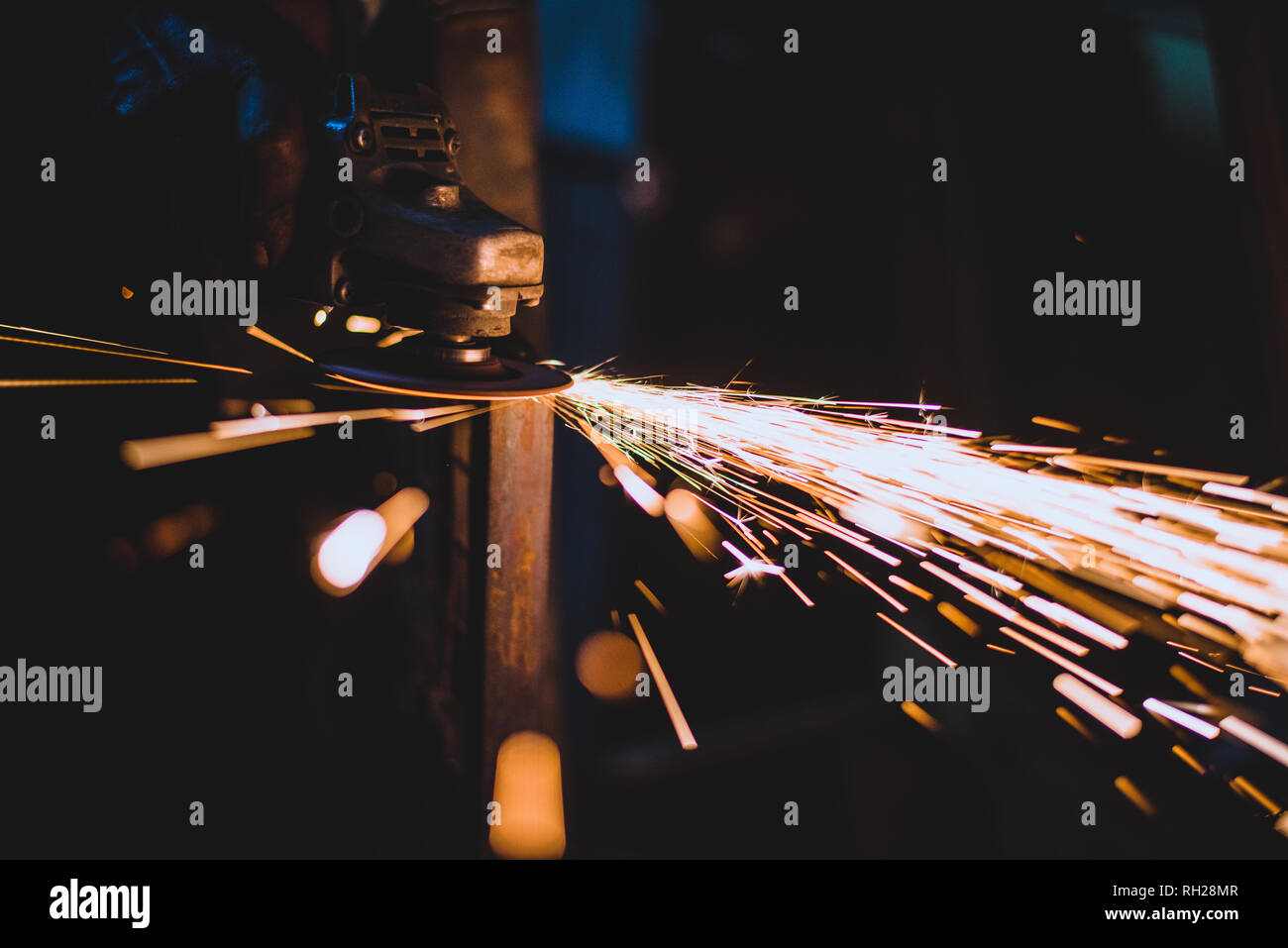 Man processes metal with an angle grinder - Stock Image