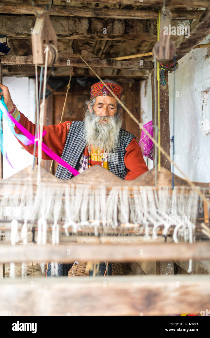 Kullu, Himachal Pradesh, India - August 09, 2018 : An Indian old man makes a traditional sadu weaving. Making A Pattu Sarees in Himalayas - Stock Image