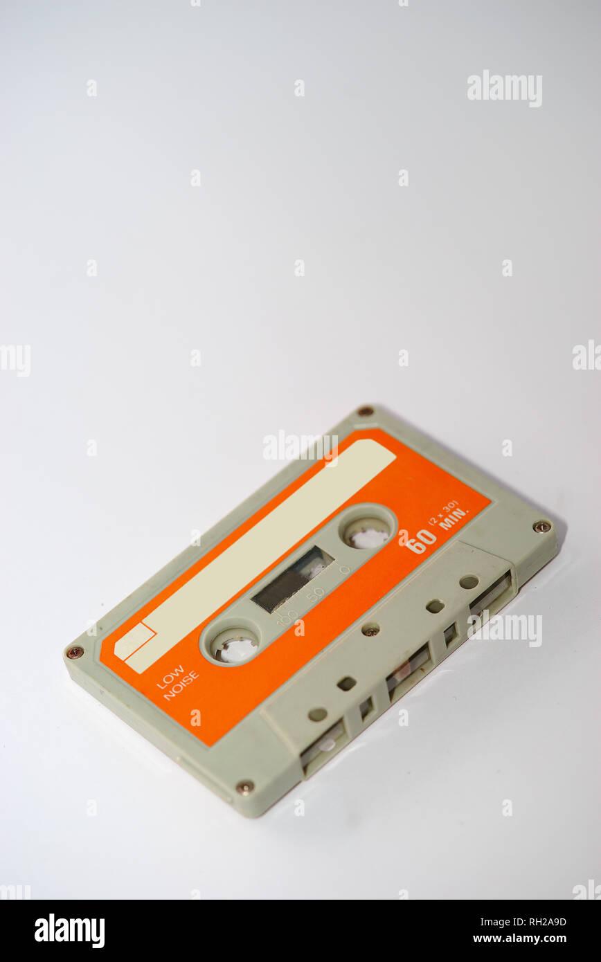grey and orange vintage audio tape on white background - Stock Image