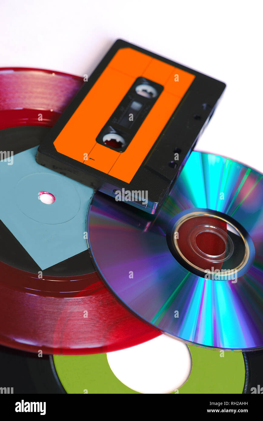 CD, red and black vinyl disc and audio tape on white background - Stock Image