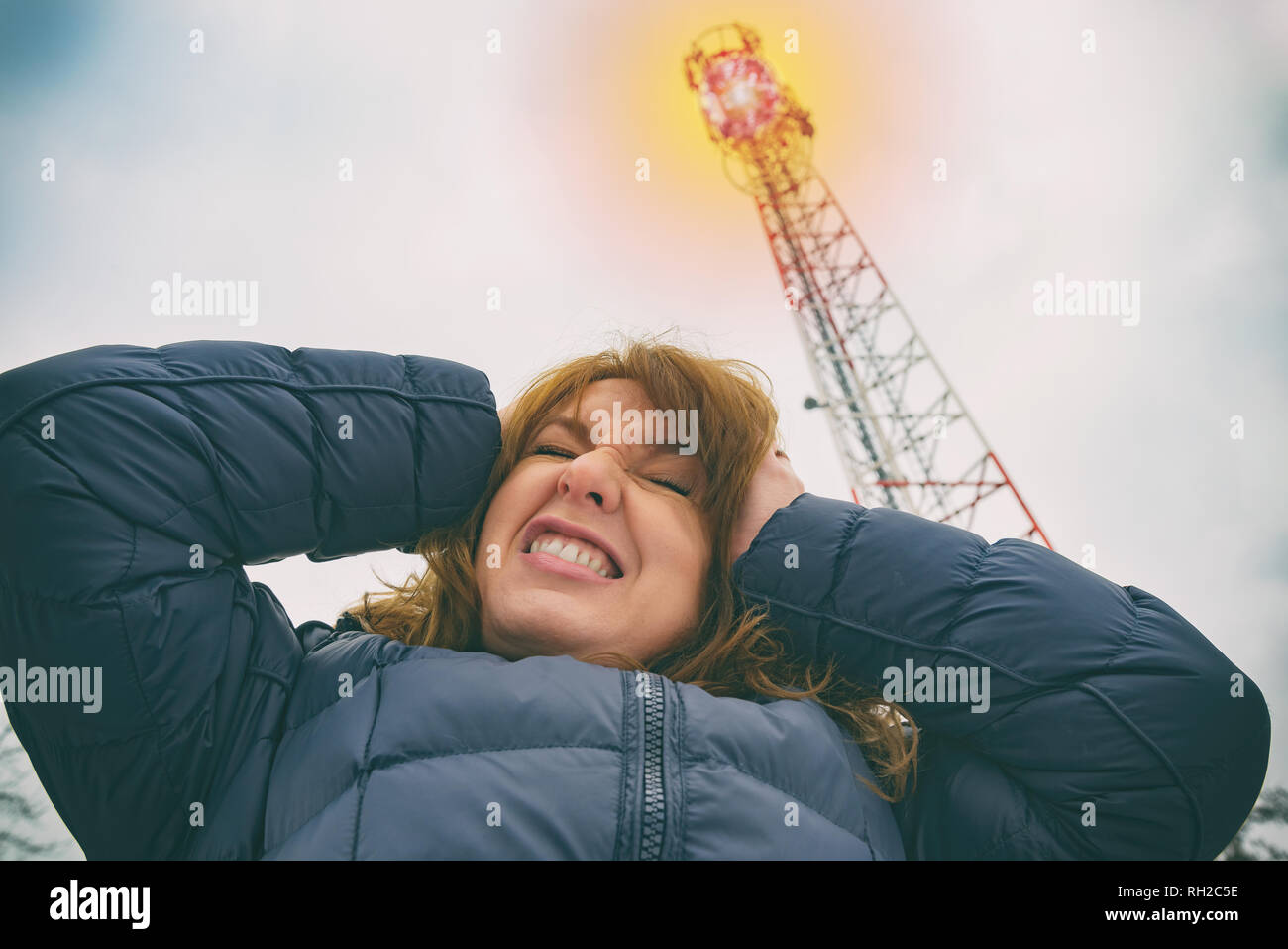 The woman is holding her head near the BTS. Harmful radiation from cellular network transmitters concept - Stock Image