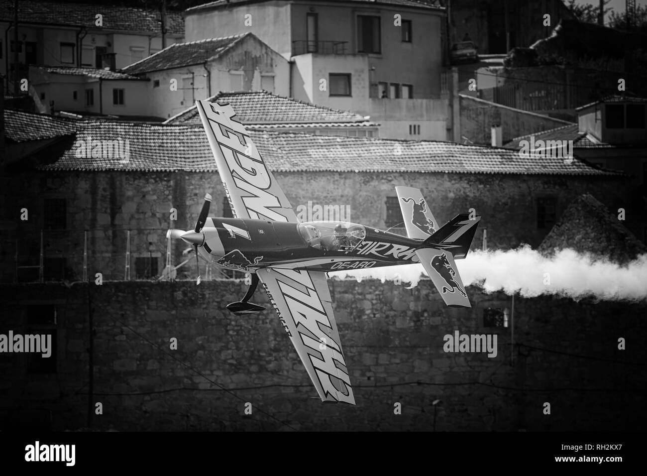 Porto, Portugal - September 1, 2017: Red Bull air race. Training day. Airplane in a tight maneuver on the Vila Nova de Gaia bank of the Douro river. - Stock Image