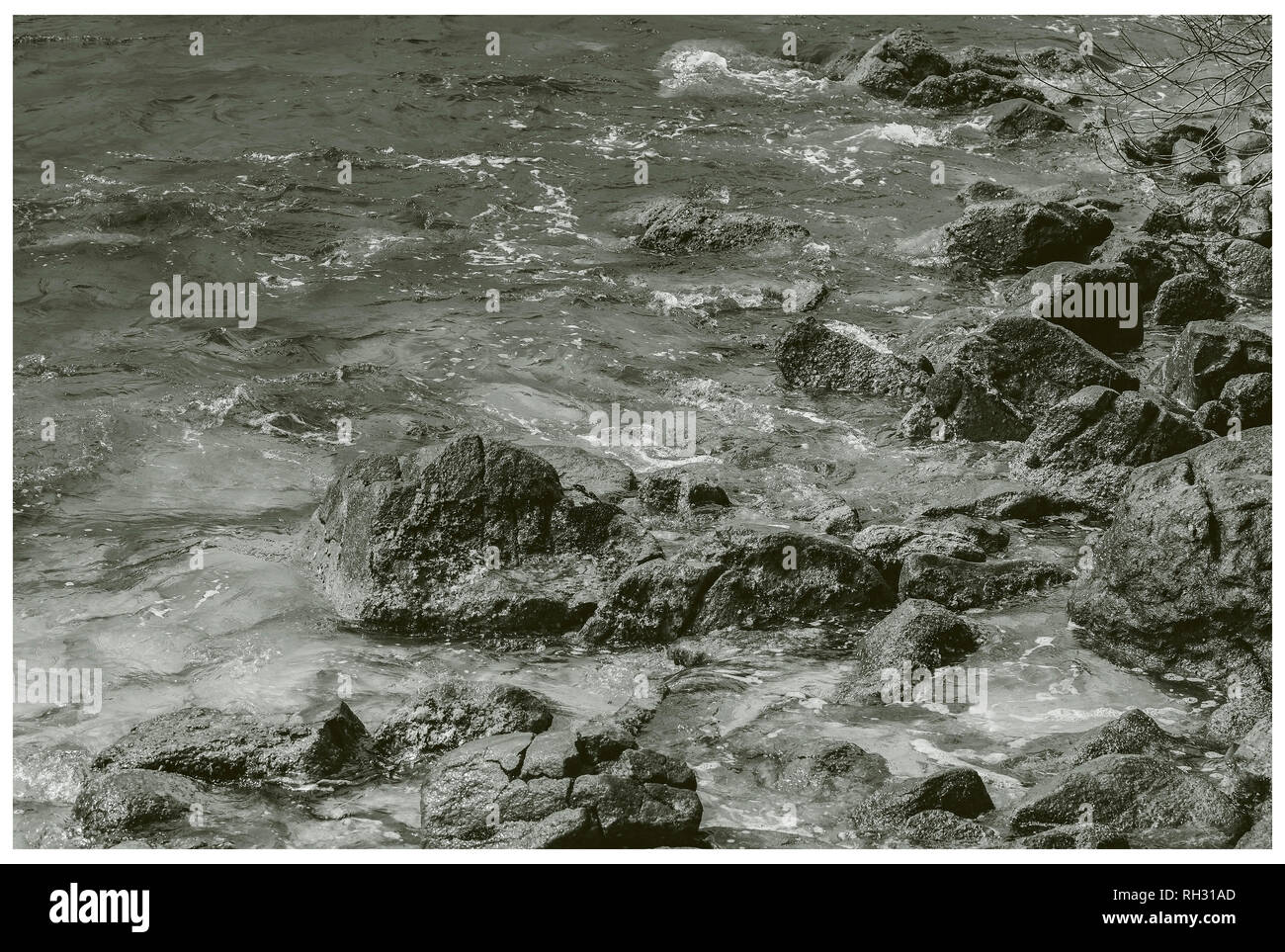 Water of the sea hitting calmly and running around the sea rocks on the coast of a beach. Frame. Vintage tones. - Stock Image
