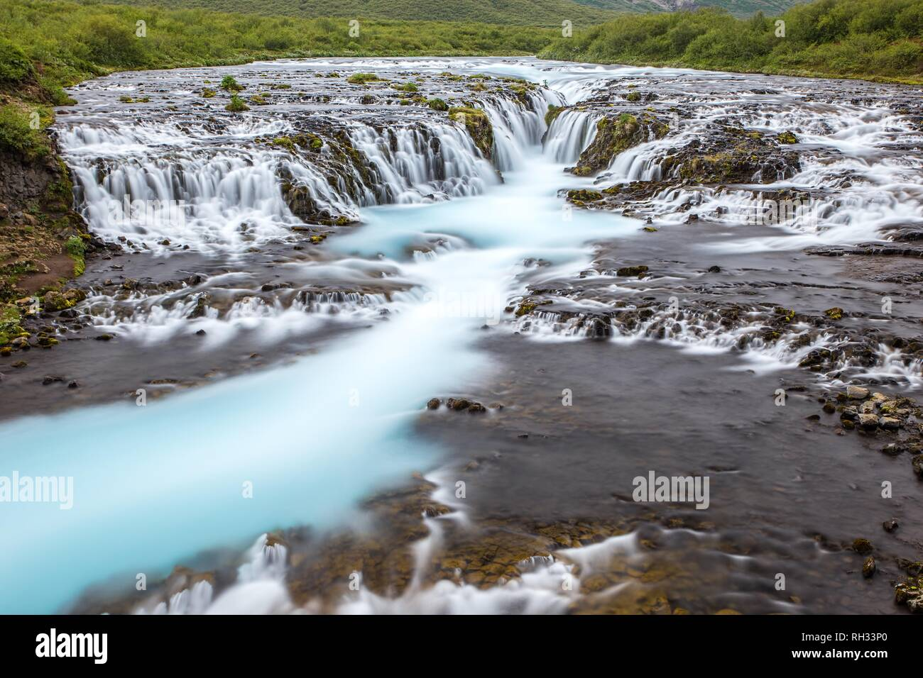 Bright powerful Bruarfoss waterfall in Iceland with cyan water. - Stock Image