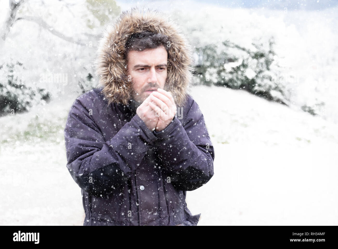 Man in cold and snowy weather storm in winter - Stock Image