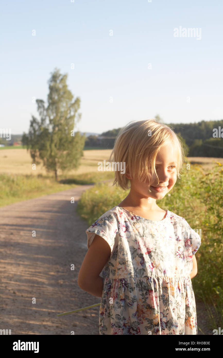 Smiling girl on dirt track - Stock Image