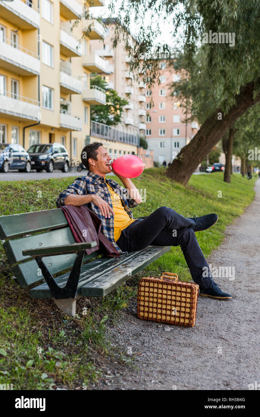 Smiling boy on bench blowing balloon - Stock Image