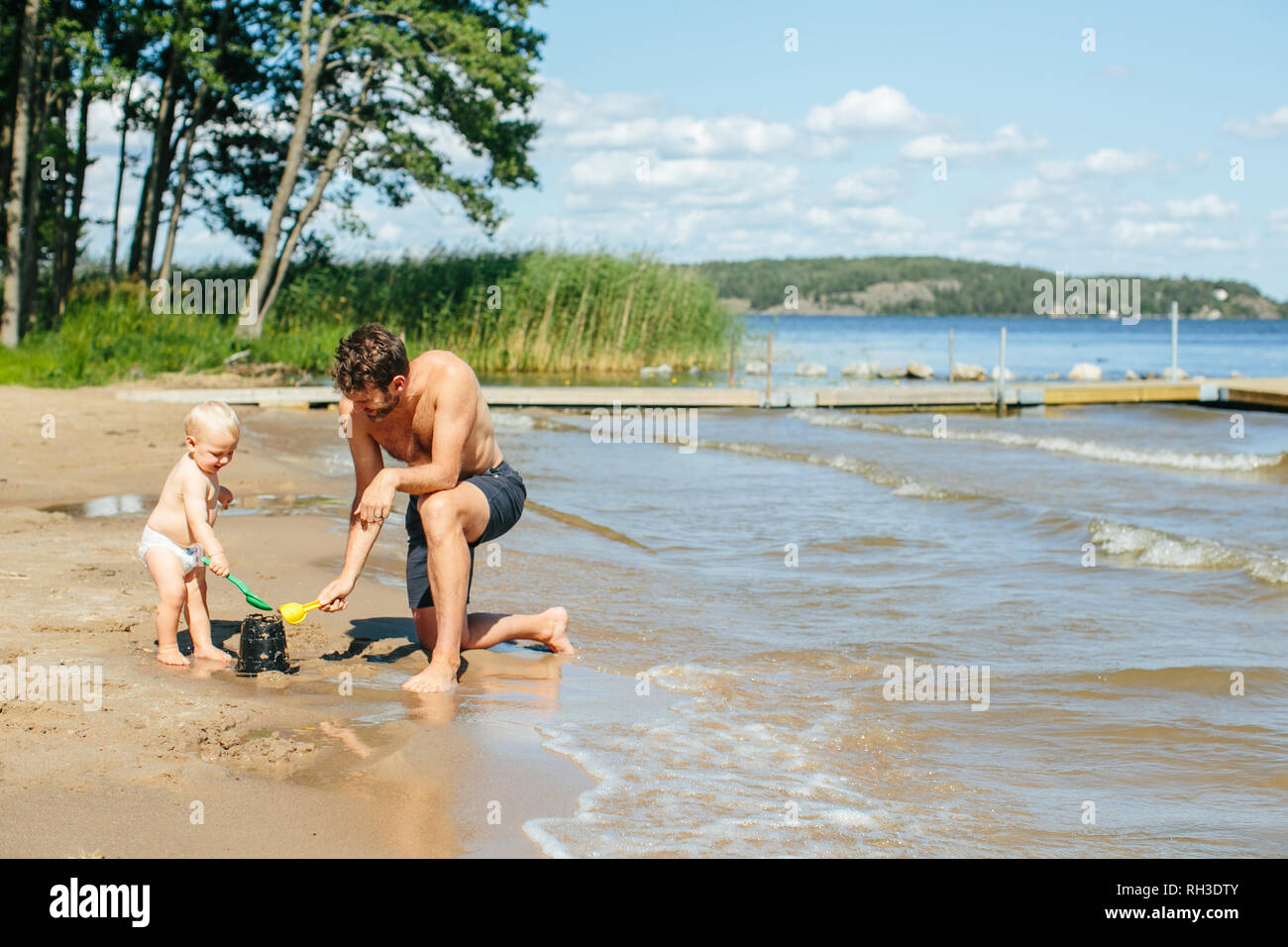 Father playing on beach - Stock Image