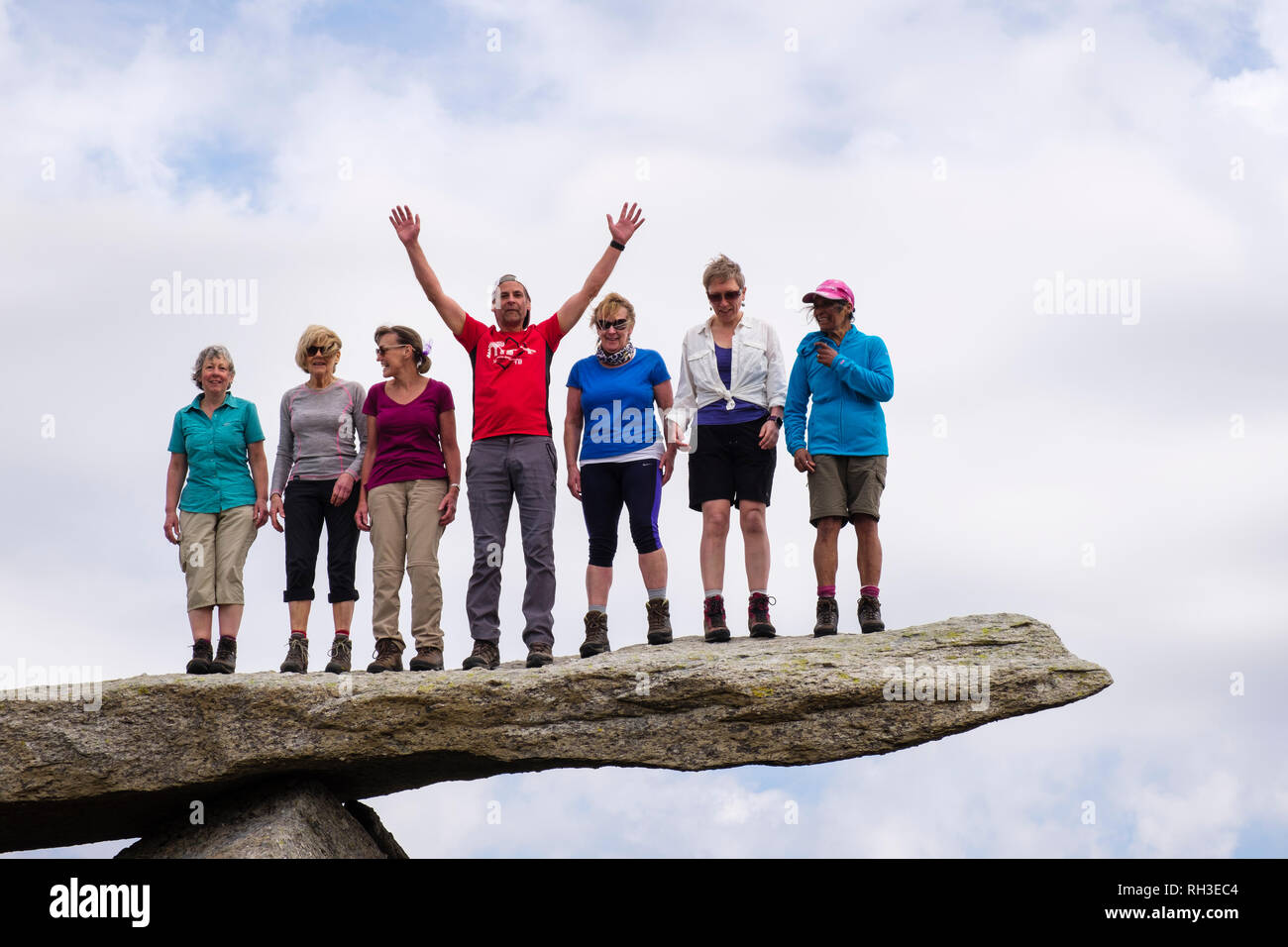 A group of happy hikers standing on the cantilever rock on Glyder Fach mountain in Snowdonia National Park. Ogwen, Conwy, Wales, UK, Britain - Stock Image