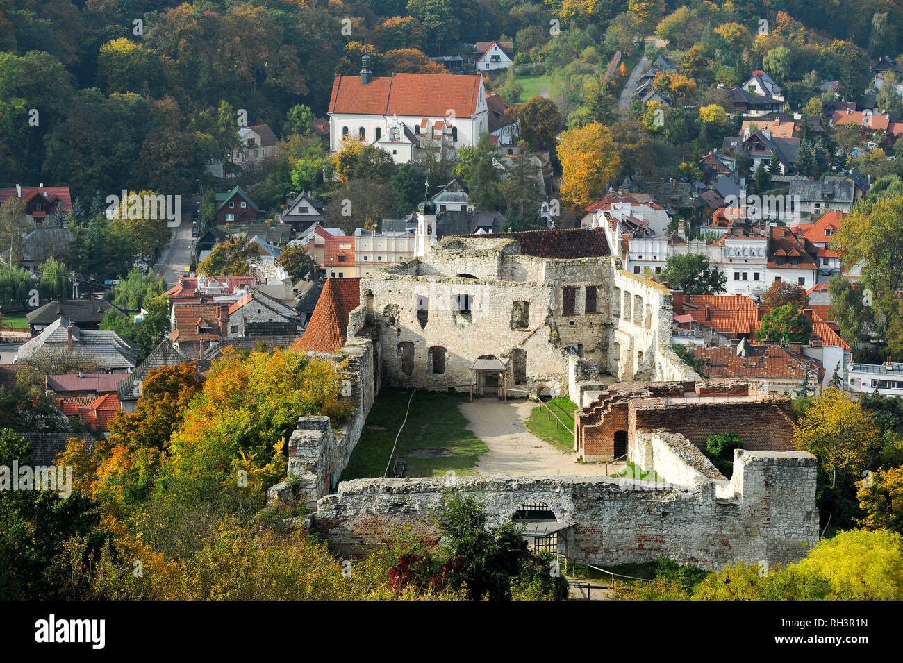 Ruins of Gothic castle built in XIV century by Polish King Kazimierz Wielki and Franciscan baroque Church of St. Mary buily 1589 and Franciscan monast - Stock Image