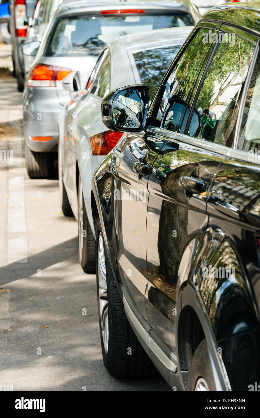 Modern cars in a row parked on Paris street during the day - Stock Image