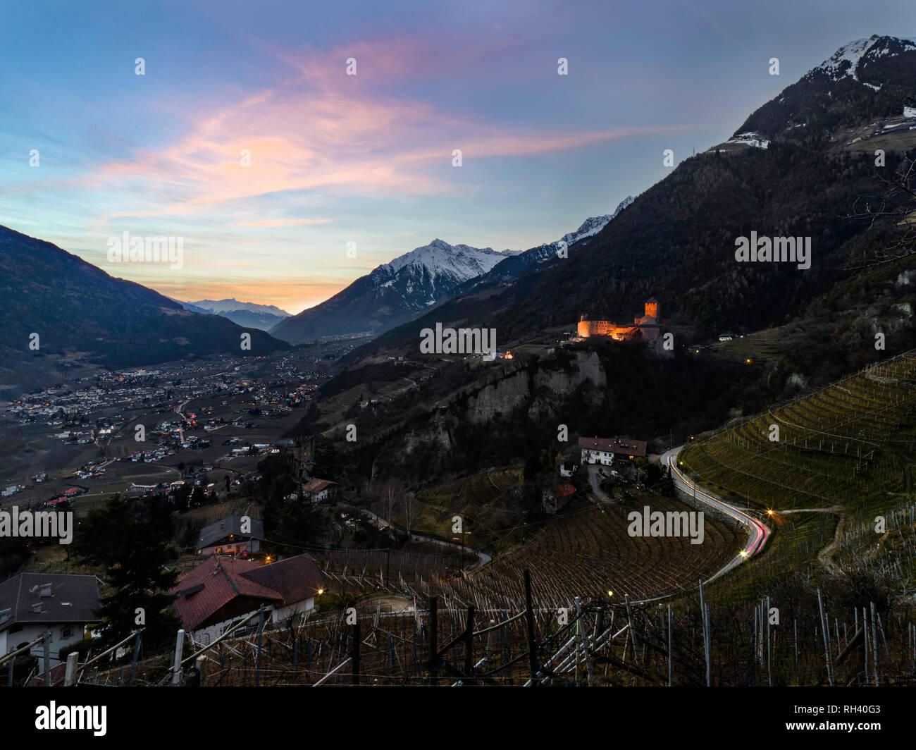 Beautiful orange purple sunset over Merano and Castle Tyrol in Alto Adige, Italy Stock Photo