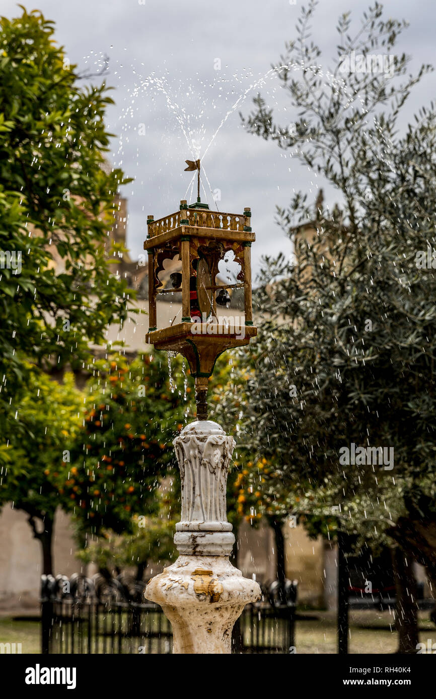 Fountain with orange trees background in a mosque garden in Cordoba Spain - Stock Image