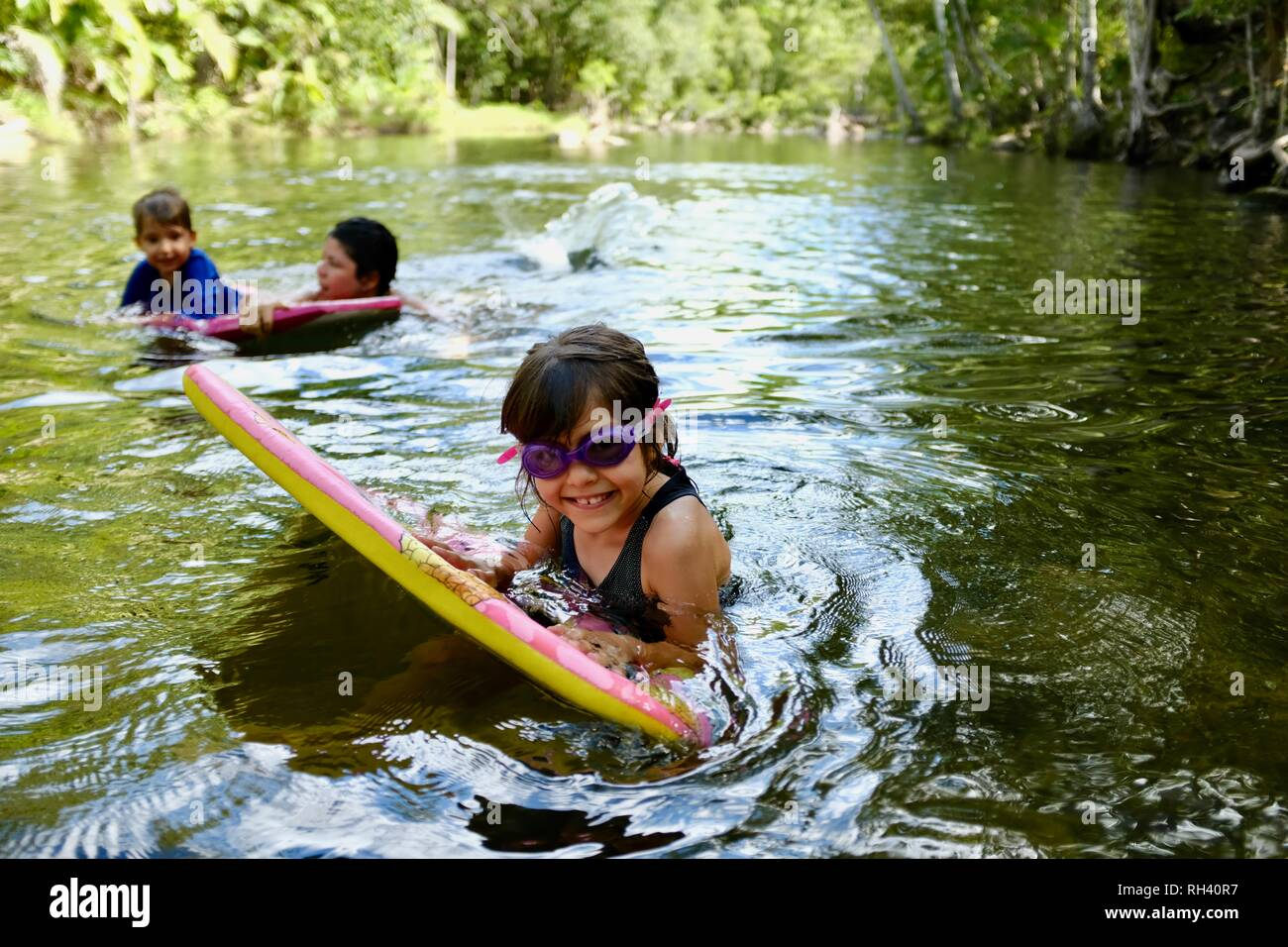Young girl paddles on a boogie board with family in background, Finch Hatton, Queensland 4756, Australia Stock Photo